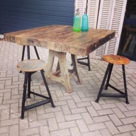 Tafel met gietijzeren onderstel en dik ruw houten blad.