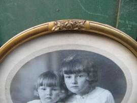 Brocante goudkleurige ovale lijst met glas en oude foto.