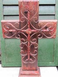 Oud rood metalen kruis van sierwerk op hout