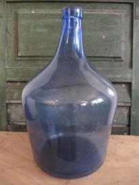 Oude glazen fles in blauw