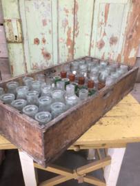 Antieke houten krat met flesjes