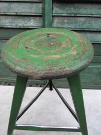 Oude metalen kruk met groene houten zitting