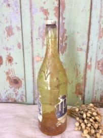 Oude limonadefles merk Whip met een gele vloeistof.