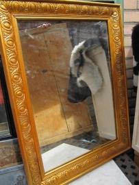 Oude spiegel in mooie bewerkte goudkleurige lijst