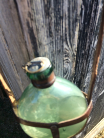 Antieke glazen veldfles met lederen tuigje