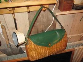 Oude tas van biezen met een groen lederenklep en koperen accenten