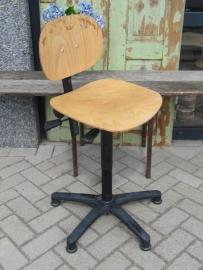 Oude industriële werkplaatsstoel met houten zitting