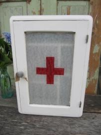 Oud medicijnkastje met glas en rood kruis