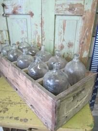 Tien spuitflessen in houten krat