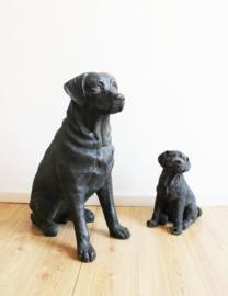 Twee levensgrote zwarte honden beelden. Vader hond met puppy.