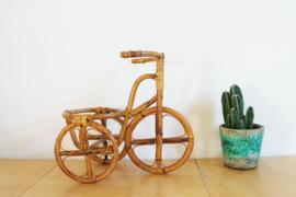 Rotan bloempot in de vorm van een fiets. Vintage plantenstandaard