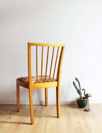 Houten vintage spijlenstoel van Lübke. Retro stoel met gebloemde zitting.