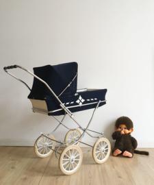 Blauw witte vintage poppenwagen. Retro wandelwagen voor de pop.