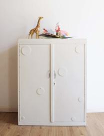 Houten retro kast met cirkeltjes op de deuren. Vintage speelgoed/kledingkast