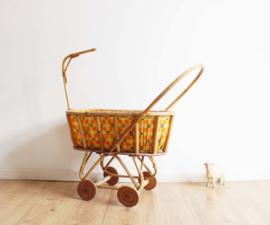Vintage rotan poppenwagen. Retro wandelwagen voor mini-papa's of mama's
