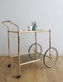 Gouden retro trolley / bijzettafel. Vintage theetafel op wielen met glazen bladen
