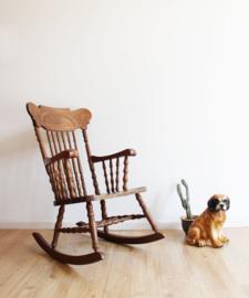 Houten vintage schommelstoel. Antieke rocking chair met houtsnijwerk.