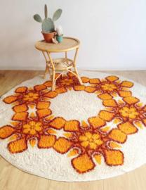 Te gek vintage vloerkleed met oranje bloemen. Rond retro seventies tapijt met bloemen