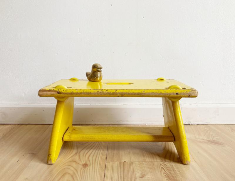 Klein knal geel bankje met wieltjes. Vintage krukje