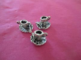 Zilverkleurig kop en schotel met lepeltje