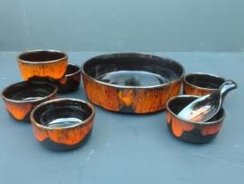 Serveerschaal met kleine schaaltjes van aardewerk.