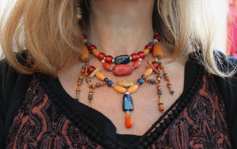 Halssnoer samengesteld uit vintage en Berber juwelen met houten, plastic, stenen en klei kralen oranje geel rood blauw
