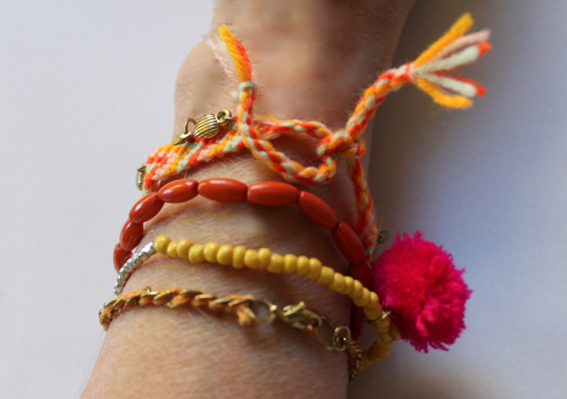 "Ibiza ""Orange"" setje van 4 armbandjes met hartjes, oranje, geel, goud met fluo roze pompon - Ibiza ""Orange"" 4-piece bracelet set with little hearts, orange, yellow,  gold with fluorescent pink pom pom​"