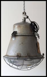 Industriële lamp , middelgrote grijze fabriekslamp met bolglas en gaas.
