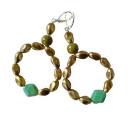 Grote ringen van goudkleurige kralen en groen glas