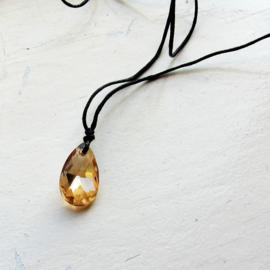 Goudgeel kristal aan een koord