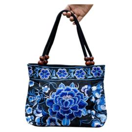 Blauwe geborduurde tas met grote roos en bloemenrand aan de bovenkant (h x b x d = 21 x 25 x 10 cm)