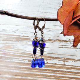 Oorbellen van blauw glas aan haken van brons (7 cm lang)