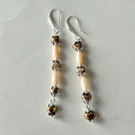 Goudkleurige zoetwaterparels met ivoorkleurige parelmoerstaafjes aan haken van sterling zilver