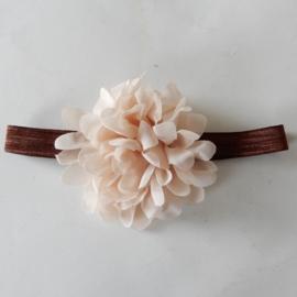 Bloem van beige voile op een bruine band van elastiek