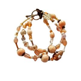 Armband met 3 strengen van roze-bruine glaskralen en kleine parelmoertjes  (18,5 cm lang)