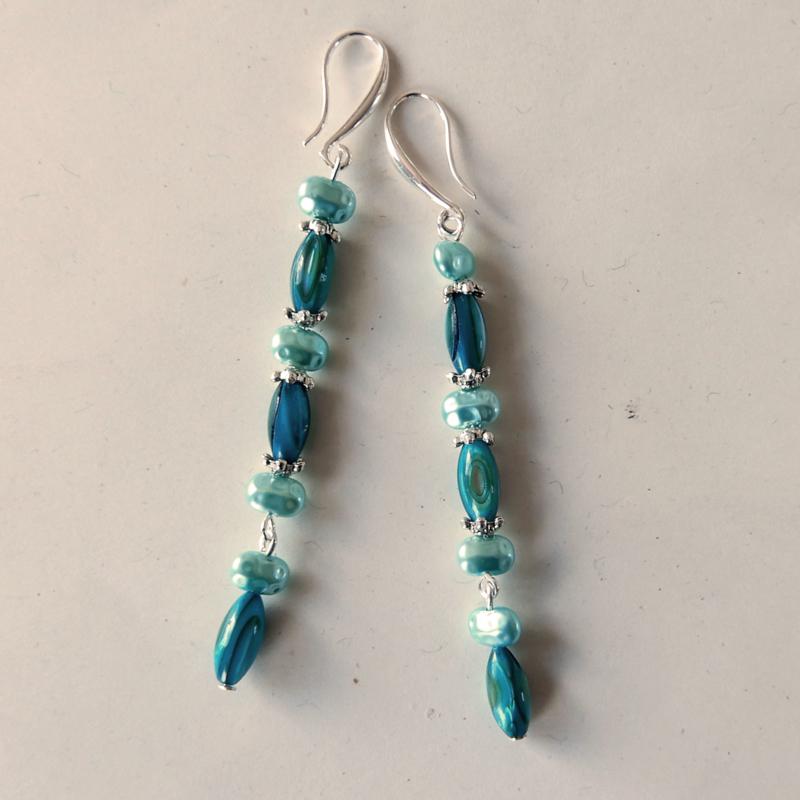 Pauwblauwe parelmoerstaafjes met blauwe zoetwaterpareltjes aan haken van sterling zilver