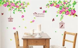 Muursticker takken met roze bloemen en vogelkooi