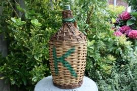 Groene fles in mand met een groene K beschilderd (art.nr. 295)