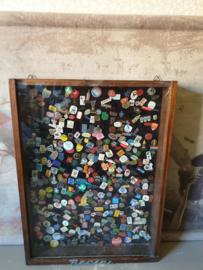 Oude houten pronkkast vol met speldjes