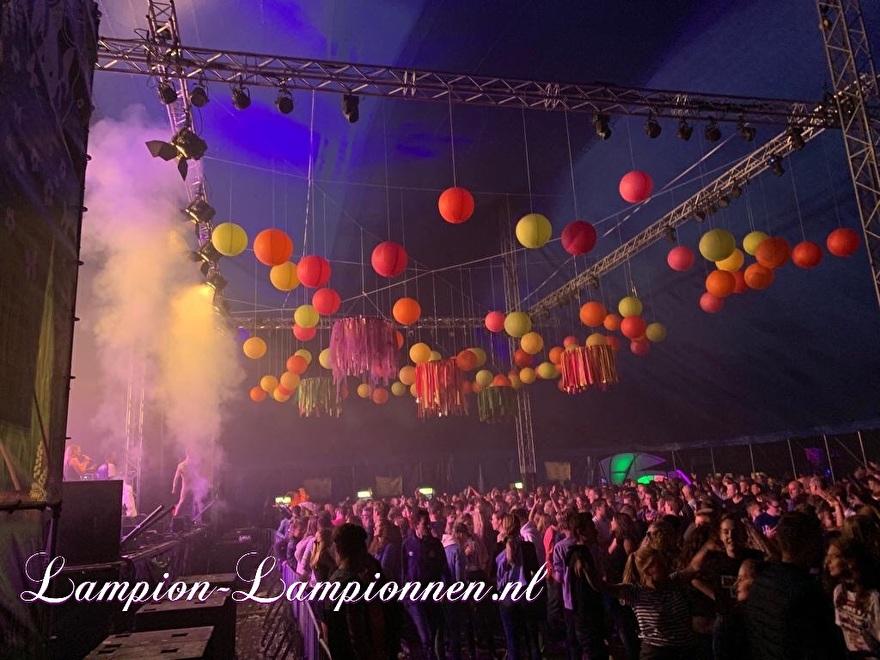 farbige laternen bei einem musikfestival-event, fabriges papier später am event, laternen und papier coleur fete, party deko mit papierlaternen rot gelb orange bühnen-event styling tanz eventplaner