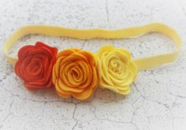 Handgemaakte haarband met drie vilten rozen in donkeroranje, oranje en geel