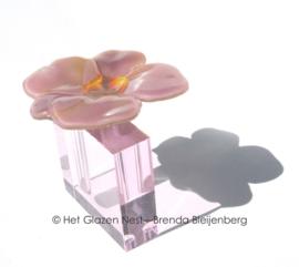 Roze glas bloem op doorzichtige roze ashouder