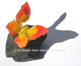 Kleine oranje vlinder op grijze steen
