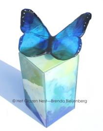 Blauwe vlinder op zee groene urn zuil