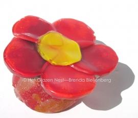 Rood bloemetje op rode voet van sandcasting