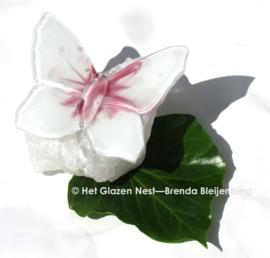 Witte vlinder met roze accenten op bergkristal