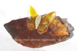 Klein geel vlindertje op een oker geel glasbrok