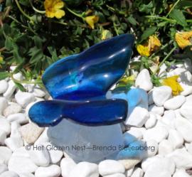 vlinder in blauwtinten op casting glas steen