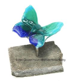 Kleine blauw groene vlinder op ruwe steen