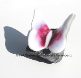 Vlinder op steen in wit en roze